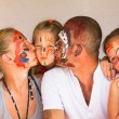 Happy family - young couple kissing younger baby daughter, after playing with paints — Стоковая фотография