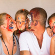 Happy family - young couple kissing younger baby daughter, after playing with paints — Foto Stock