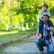 Stock Photo: Portrait of father and son in the park.