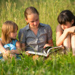 Children reading book in natural environment together. — Стоковая фотография