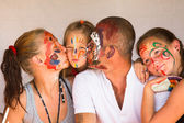 Happy family - young couple kissing younger baby daughter, after playing with paints — Stock Photo