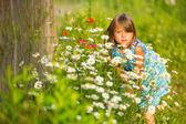 Charmante petite fille parmi les fleurs sauvages jaunes — Photo