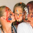 Happy family - young couple kissing baby daughter, after playing with paints. — Foto de Stock