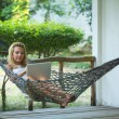Foto Stock: Girl lies in the hammock with laptop