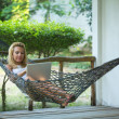 Girl lies in the hammock with laptop — ストック写真