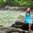 Teen-girl in a blue dress in the rocks of the coast — Stock Photo