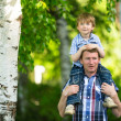Stok fotoğraf: Portrait of father and son outdoors.