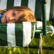 Close-up portrait of little girl lying on a swing in the yard of a country house — Stock Photo #28999463