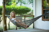 Girl lies in the hammock with laptop — Stok fotoğraf