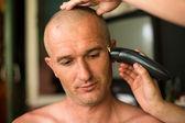Hairdresser shaving man with hair trimmer. — Stock Photo