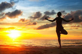 Young woman practicing yoga on the beach during the sunset. — ストック写真