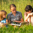 Children reading book on the park together. — Zdjęcie stockowe