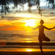Young woman practicing yoga at sunset on the coast of Thailand — Stock Photo