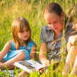 Portrait of three cute little girls reading book — Stok fotoğraf