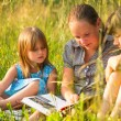 Portrait of three cute little girls reading book — Stock Photo #29272409