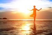 Silhouette woman practicing yoga — Stock Photo