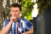 Man smoking outdoor in the park. — Stock Photo