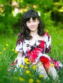 Beautiful girl sitting in the grass — Stock Photo