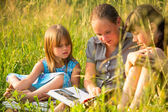 Portrait of three cute little girls reading book — Stock Photo