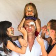 Stockfoto: Children paints face of his father (Happy family concept)