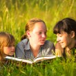 Three little sister reading book in natural environment together — Stok Fotoğraf #29975803
