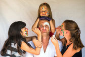 Children paints face of his father (Happy family concept) — Stock Photo
