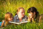 Tři malá sestra čtení knih v přirozeném prostředí společně — Stock fotografie