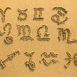 Stock Photo: Set of zodiac signs drawn on the facture beach sand