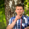 Man smoking outdoor in the park, looking at the camera. — Стоковое фото