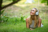 Beautiful emotional girl with headphones in the park at sunny day. — Stock Photo