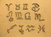 Zestaw znaków zodiaku na piasku plaży dokumentu faktury — Zdjęcie stockowe