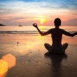 Silhouette young woman practicing yoga, on the beach at sunset — Stock Photo #30692999