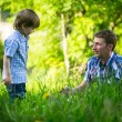 Father playing with his small son in grass — Stok Fotoğraf #30693205
