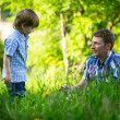 Stockfoto: Father playing with his small son in grass