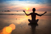 Silhouette young woman practicing yoga, on the beach at sunset — Stock Photo
