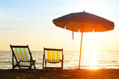 Pair of beach loungers on deserted coast sea at sunrise — Stock Photo
