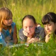 Photo: Three little sister reading book in natural environment together.