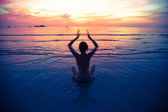 Sunset yoga woman on sea coast (cross process stile) — Stock Photo