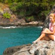 Photo: Beautiful blonde girl is sitting on the rocks at the seaside