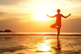 Backlit, young woman practicing yoga on the beach at sunset. — Stock Photo