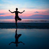 Silhouette of a woman yoga on sea sunset with reflection in water. — Stock Photo