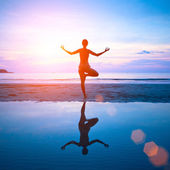 Young woman practicing yoga on the beach at sunset with reflection in water. — Stock Photo
