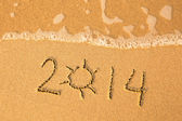 2014 written in sand on beach texture, soft wave of the sea. — Stock Photo