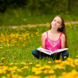 Stock Photo: Girl sits on grass and dreams while reading book