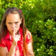 Beautiful young girl with her finger over her mouth, hushing — Stock Photo