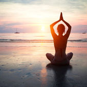 Silhouette of a woman yoga on sea sunset. — Stock Photo
