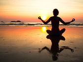 Young yoga woman sitting on sea coast at sunset — Stock Photo