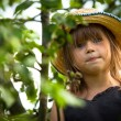 Little lovely girl posing in a straw hat in the park — Stock Photo #31223473