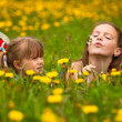 Little sisters blowing dandelion seeds away in the meadow. — Foto de Stock