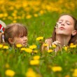 Little sisters blowing dandelion seeds away in the meadow. — Foto Stock